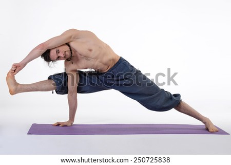 An attractive athletic man doing a yoga pose in studio on white background.
