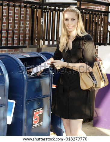 An attractive blond woman mails a letter.