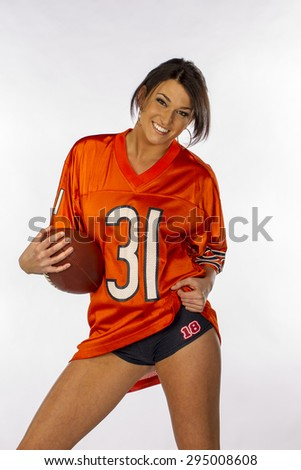 An attractive brunette model posing with a football in a studio environment - stock photo