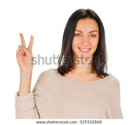 An attractive brunette young woman showing sign of victory on white background - stock photo