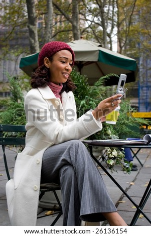An attractive business woman checking her cell phone in the city.  She could be text messaging or even browsing the web via wi-fi or a 3g connection. - stock photo
