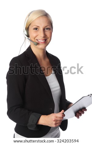 An attractive businesswoman in her 20s, wearing a black jacket with a headset holding a clipboard smiling towards camera. White background. - stock photo