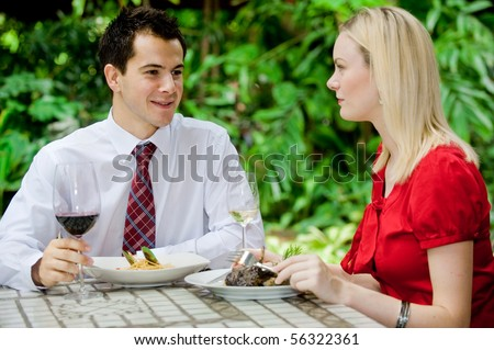 An attractive caucasian couple having a meal with wine at an outdoor restaurant - stock photo