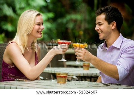 An attractive caucasian couple having drinks and relaxing at an outdoor restaurant
