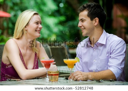 An attractive caucasian couple having drinks and relaxing at an outdoor restaurant - stock photo