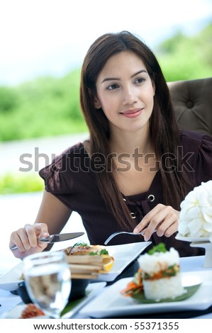 An attractive caucasian woman having a relaxing meal outdoors - stock photo