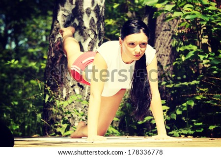 An attractive caucasian woman practicing yoga outdoors  - stock photo