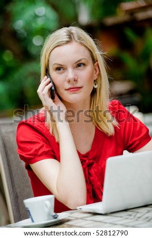 An attractive caucasian woman talking on the phone and using her laptop at an outdoor restaurant - stock photo