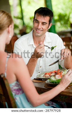 An attractive couple having dinner together at a restaurant - stock photo