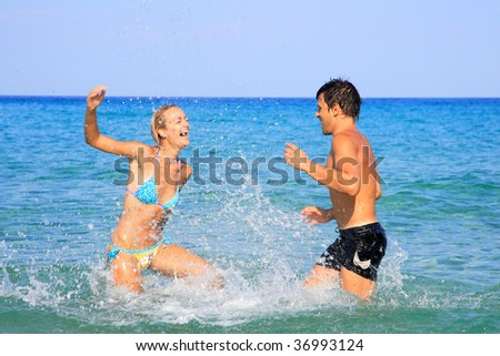 An attractive couple playing on the beach