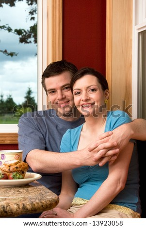An attractive couple smiling over breakfast.  The man is hugging the woman.  Vertically framed shot. - stock photo