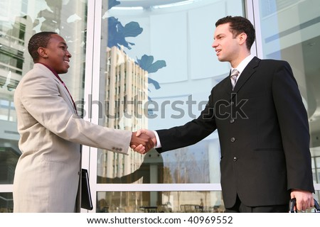 An attractive, diverse business man team shaking hands at office building - stock photo