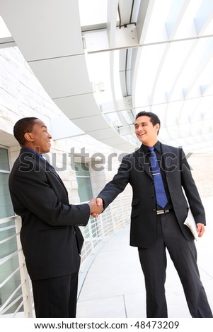 An attractive, diverse business man team shaking hands at office building