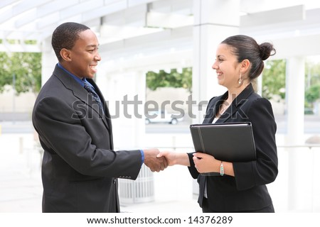 An attractive, diverse, business team man and woman handshake