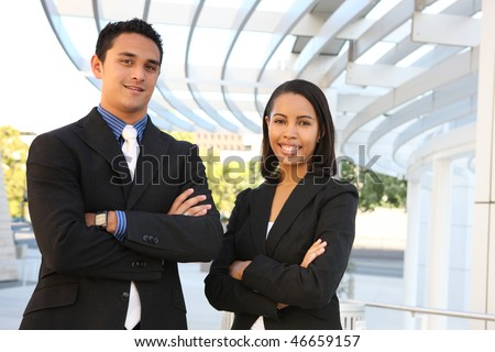 An attractive, diverse man and woman business team at their company office building - stock photo