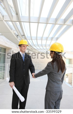 An attractive, diverse man and woman construction team shaking hands - stock photo