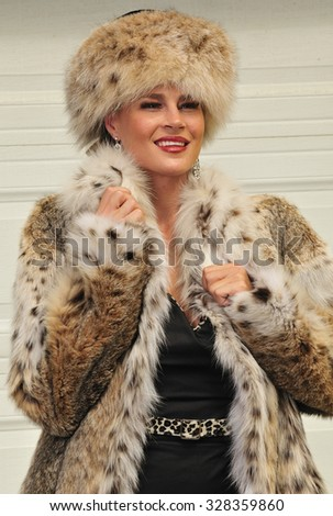 An attractive eastern European woman wearing a fashionable fur coat and fur hat - stock photo