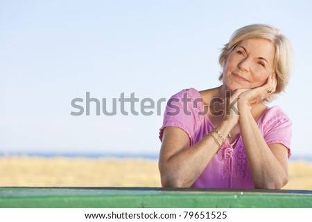 An attractive elegant and happy senior woman sitting outside out a table and thinking, behind her is a beach and the sea - stock photo