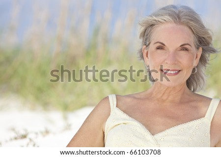 An attractive elegant senior woman sitting on a white sand beach with grass and a blue sky behind her. - stock photo