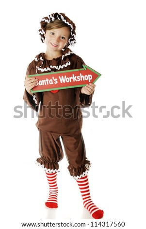 """An attractive elementary """"gingerbread girl"""" holding a sign that points to Santa's Workshop.  On a white background. - stock photo"""