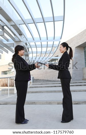 An attractive ethnic business women team at office building with report - stock photo