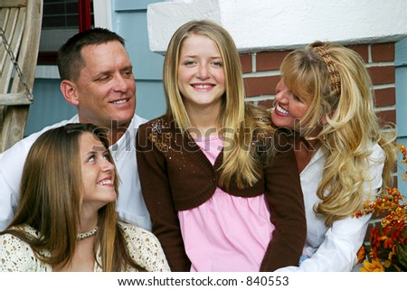 An attractive family all looking at the youngest girl in the center of the group.