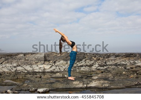 An attractive female doing yoga on the beach - stock photo