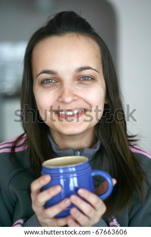 An attractive female having a cup of tea or coffee - stock photo