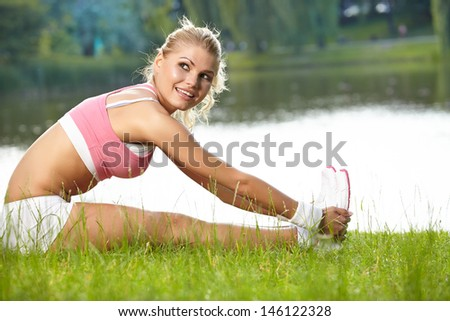 An attractive female runner stretching before her workout  - stock photo