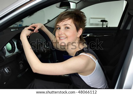 An attractive, friendly auto mechanic checking the engine of a car