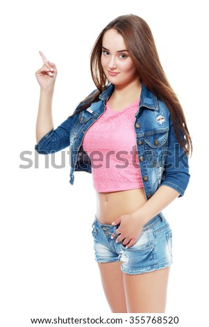 An attractive girl pointing. Smiling blond young woman in  jeans shorts,  pink top standing and pointing. Side view.  - stock photo