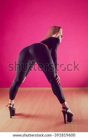 An attractive girl with a good figure is dancing near the pylon on a background of a pink wall seductive dance - stock photo
