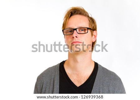 An attractive handsome man poses in the studio for a portrait against an isolated white background while wearing a black shirt and a grey cardigan sweater. - stock photo