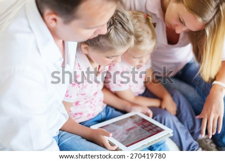 An attractive happy family of mother, father and daughters sitting on a sofa at home having fun using a tablet computer. DOF. Close up - stock photo