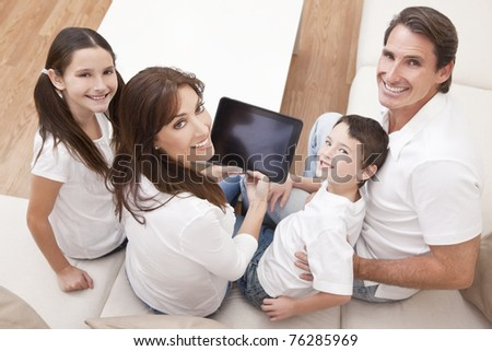 An attractive happy, family of mother, father, son and daughter sitting on a sofa at home having fun using a tablet computer - stock photo