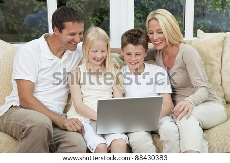An attractive happy, family of mother, father, son and daughter sitting on a sofa at home having fun using a laptop or computer