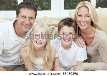 An attractive happy family of mother, father, son and daughter sitting on a sofa at home having fun
