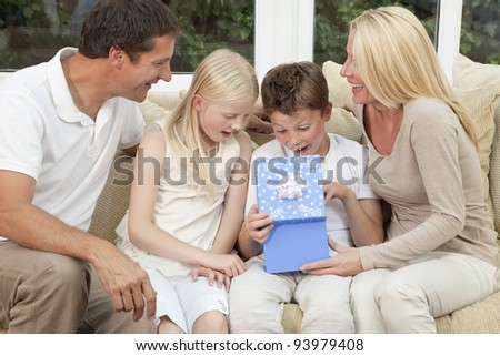 An attractive happy, family of mother, father, son and daughter sitting on a sofa at home the boy child is opening a birthday present in a blue box - stock photo