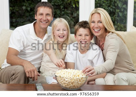An attractive happy family of mother, father, son and daughter sitting on a sofa at home watching a film or television and eating popcorn. - stock photo