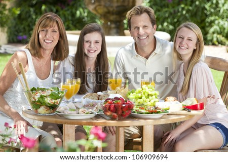 An attractive happy, smiling family of mother, father and two daughters eating healthy food at a table outside. - stock photo