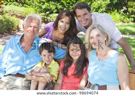 An attractive happy, smiling family of mother, father, grandparents, son and daughter sitting on a bench outside in the sunshine. - stock photo