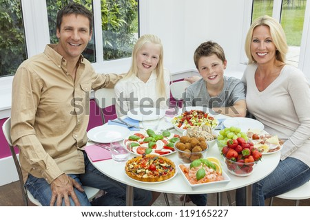 An attractive happy, smiling family of mother, father, son and daughter eating healthy salad at a dining table.