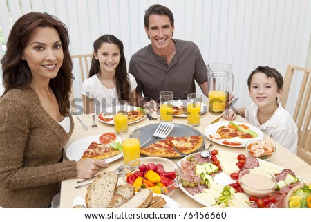 An attractive happy, smiling family of mother, father, son and daughter eating salad and pizza at a dining table. - stock photo