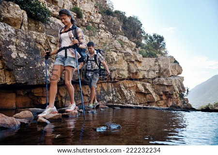 An attractive hiking couple balancing on rocks to get across the water with copyspace - stock photo