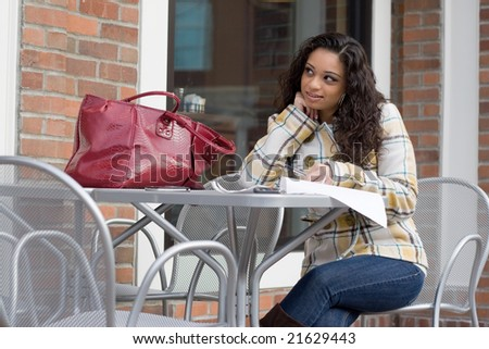 An attractive Indian woman looking over some paperwork while seated at a table outdoors. - stock photo