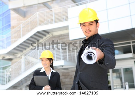 An attractive man and woman architects on a construction site