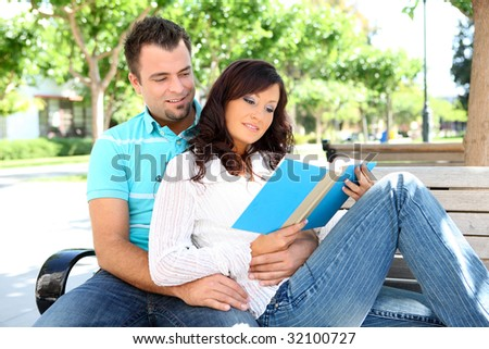 An attractive man and woman boyfriend and girlfriend reading in the park - stock photo