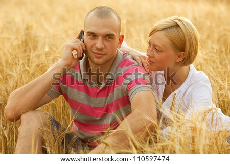 An attractive man and woman couple in the wheat field. Man holding a mobile (cell) phone in his hand and calling - stock photo