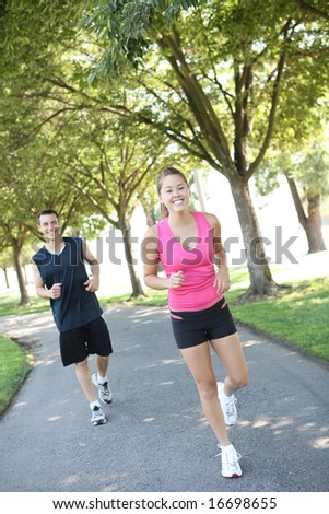 An attractive man and woman couple jogging in the park