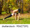 An attractive  man and woman practice Yoga in forest - stock photo